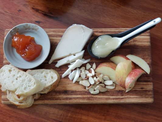 cheese plate with almonds, apples, cheese, honey, bread and mango-guava-passionfruit jam