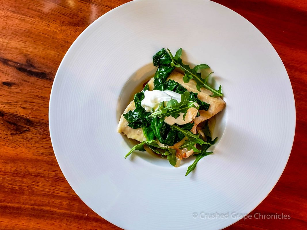 The elegant pôchouse. Rainbow trout, on a base of mushrooms, onions and bacon, in a white wine sauce topped with spinach butter, sour creme & arugula