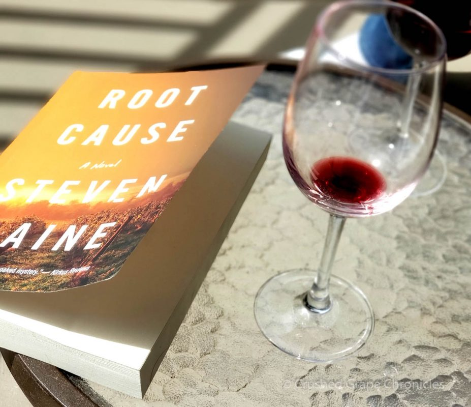 A glass of wine and Steven Laine's book Root Cause, on the balcony overlooking the pool.