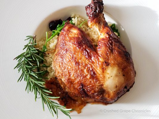 Roasted chicken on a bed of cous cous with rosemary, cranberries and arugula