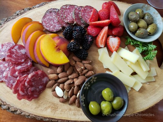 Cheese & Charcuterie platter with olives, peaches, blackberries, strawberries, emmental, wild boar sausage & almonds.