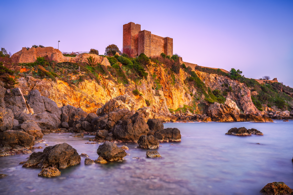 Talamone rock beach and medieval fortress at sunset. Maremma Argentario Tuscany Italy