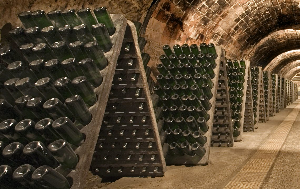 botellas apiladas en la bodega riddling racks in a cellar