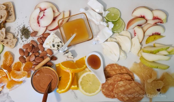 Tasting platter to pair with sparkling wines with sourdough, lobster pate, bleu cheese, lime, honey, peach, nectarine, mandarin orange, pear, crystallized ginger, apple, lemon curd orange, mozzarella, almond nougat, waffle cookies, sourdough bread, thyme, lemon, almonds and apple.