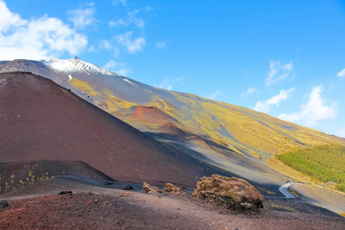 Amazing volcanic landscape on Mount Etna, Sicily, Italy taken from adjacent Silvestri craters on a sunny day. Snow on the very top of the mountain. European highest active volcano. Photo  By ppohudka Adobe Stock