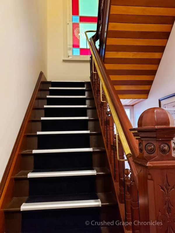 Wooden stairs with stained glass windows in the Heritage wing at the Byng Street Boutique Hotel in Orange, NSW, Australia