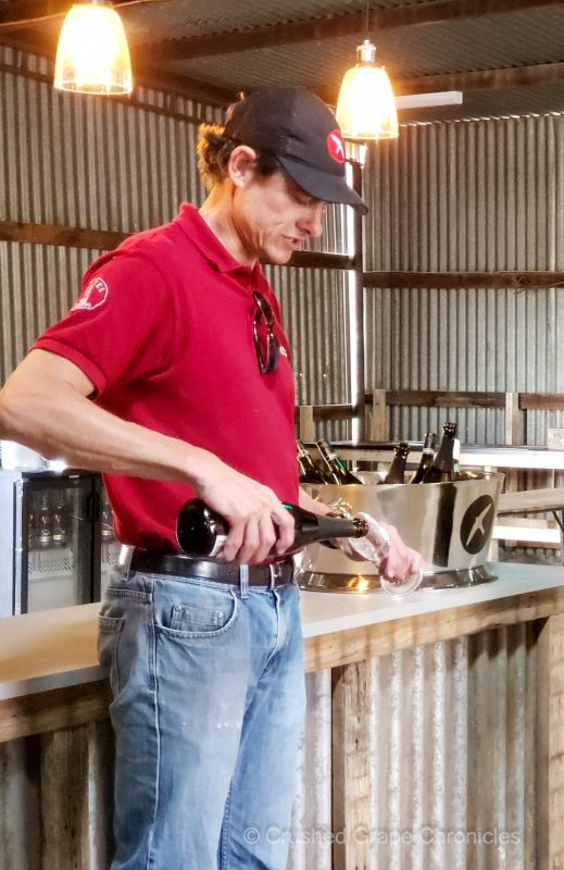 Drew Tuckwell, the winemaker for Printhie and Swift, pouring a Swift Sparkling wine. In Orange NSW Australia