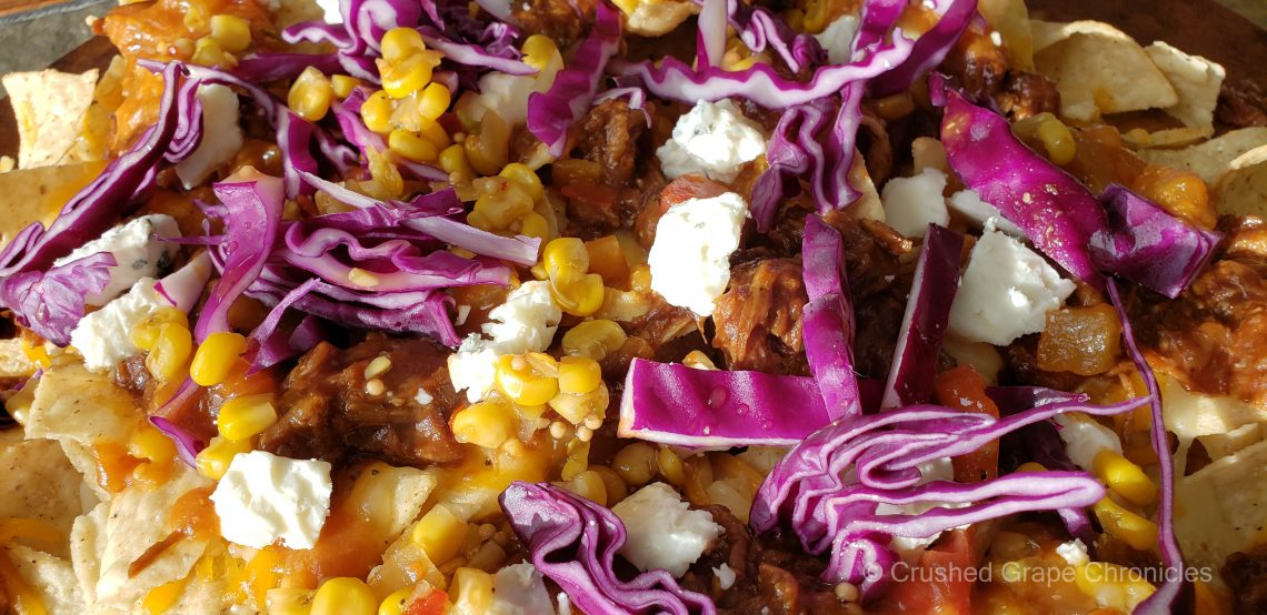 Pulled pork nachos with blue cheese and purple cabbage, sweet corn relish and harvest veggie salsa