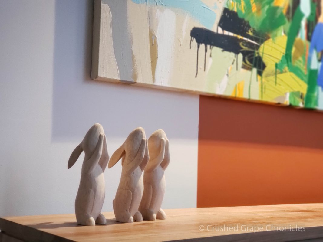 side table with 3 rabbit figurines and a modern painting at the Byng Street Boutique Hotel