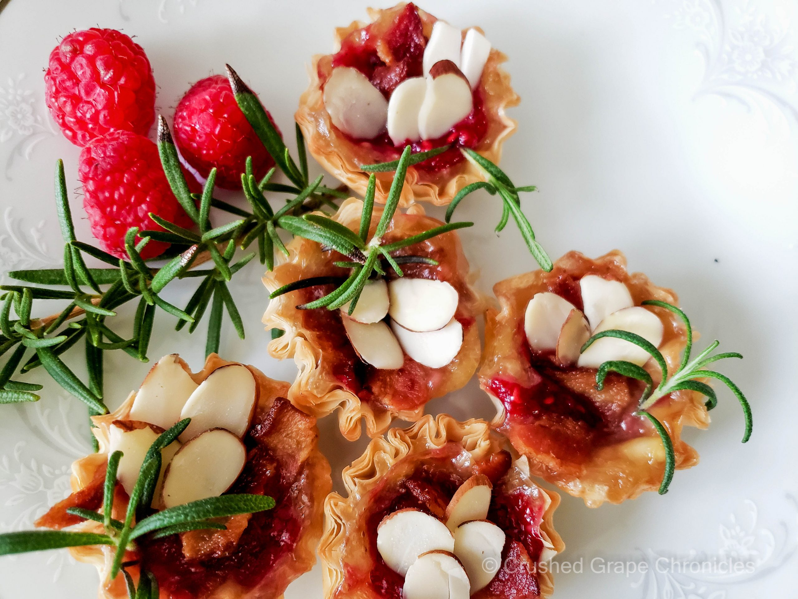 Phyllo cups filled with brie, raspberry sauce, bacon, rosemary and almonds