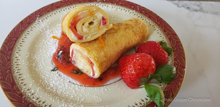 Mascarpone crepes with orange zest and strawberry sauce