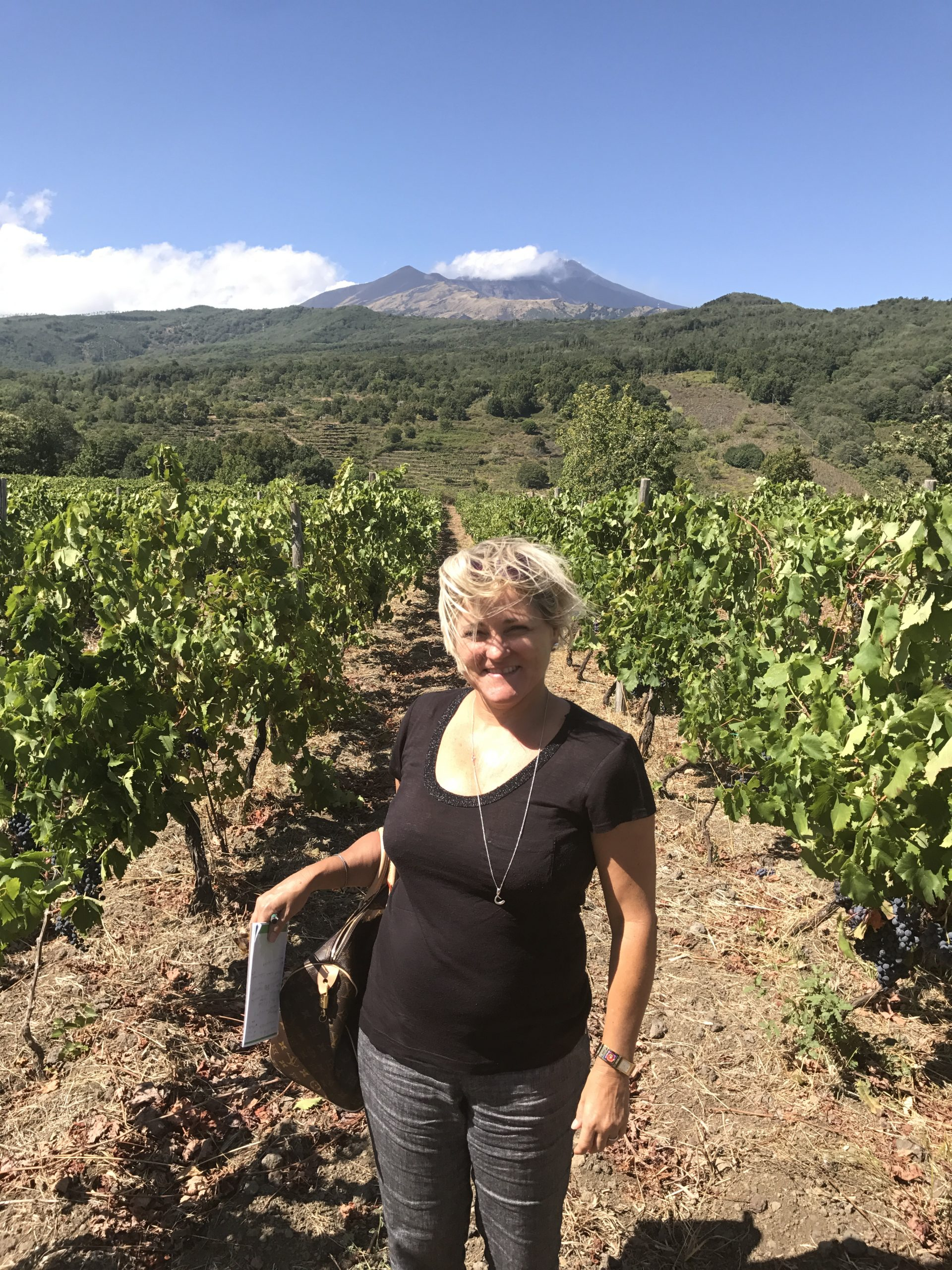 Sheila Donohue of Vero in a vineyard in front of the volcano Etna (photo courtesy Sheila Donohue)