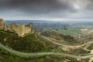 Aerial panorama view of the ruined medieval abandoned Montearagon castle, namesake of the famous kingdom on a bare mountain top near Huesca, Aragon province Spain with stormy cloudy sky - photo Adobe Stock by tamas