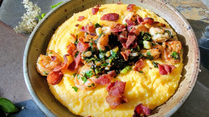 Shrimp cooked in bacon fat with cheesy grits