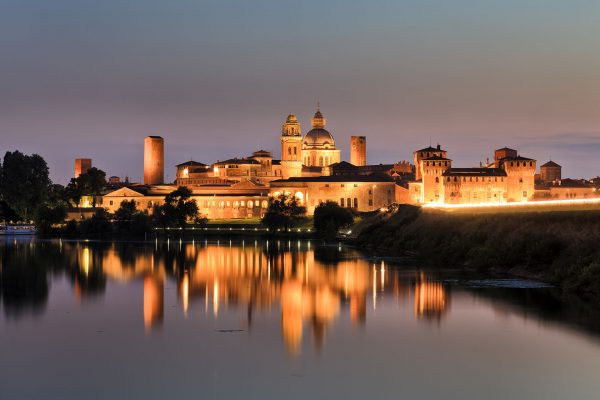 Europe Italy Mantova-Mantua ancient castle at the river reflecting in still waters at sunset highly illuminated by lights (adobe Stock by Taras Vyshnya)