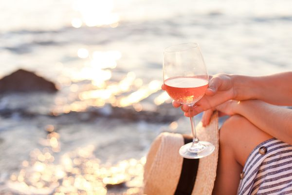 Girl is sitting on sea beach with wineglass of Rose at sunset in summer vacation in resort.